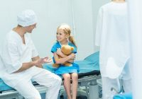 Doctors Preparing Smiling Kid For Surgery In Operating Room