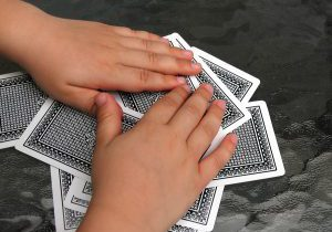 closeup of two kid hands over a pile of playing cards