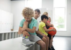 Sad pupil sitting in front of his classmates.