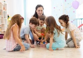 Preschool Teacher Plays With Group Of Children Sitting On A Floo